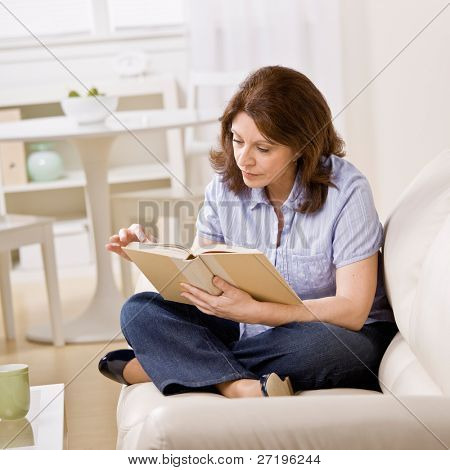 Relaxed woman sitting on sofa in livingroom enjoying reading book
