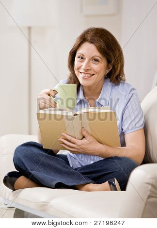Relaxed woman sitting on sofa in livingroom enjoying reading book and drinking coffee