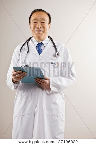 Confident doctor wearing lag coat and stethoscope holding medical chart