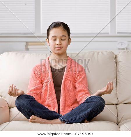 Relaxed girl sitting cross-legged meditating on sofa in livingroom