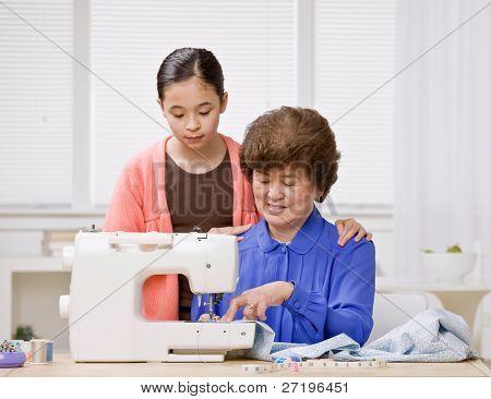 Neugierig Enkelin gerade kreative Großmutter Verwendung Nähmaschine zu Kleidung