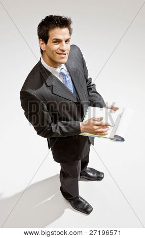 Confident businessman writing on clipboard