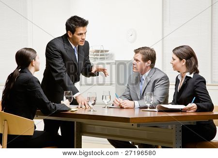 Co-workers listening to supervisor explain problem in conference room