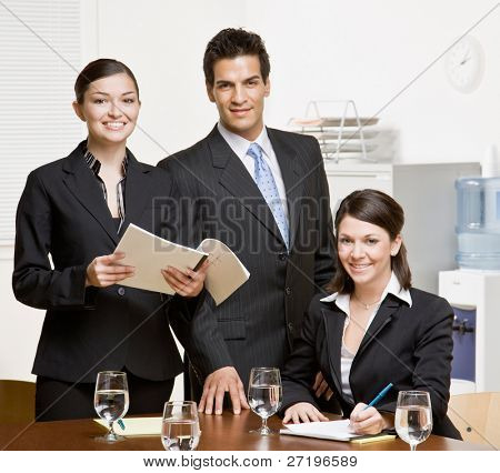 Confident co-workers with paperwork in conference room
