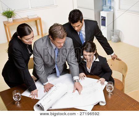 Architect explains problem on blueprint to co-workers in conference room
