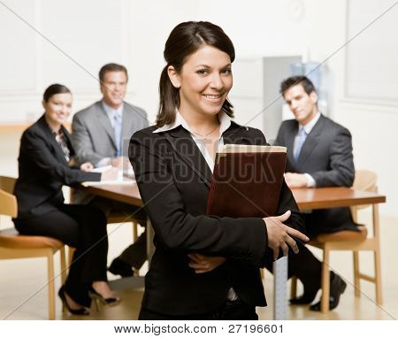 Confident businesswoman with notebook and co-workers in conference room