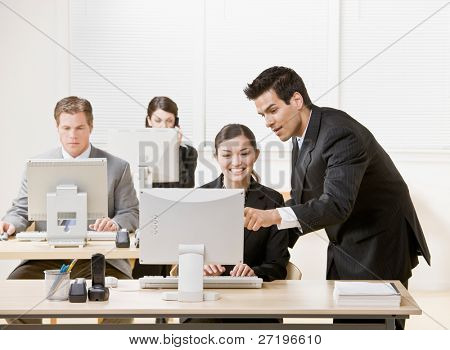 Co-worker listening to supervisor explain problem on computer