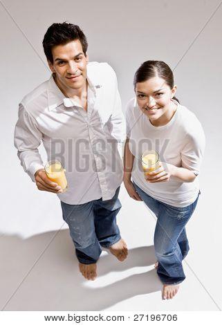 Happy barefoot couple drinking glasses of wholesome orange juice