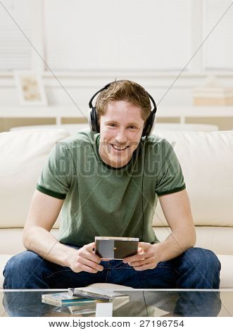 Relaxed man sitting on sofa and listening to music on headphones