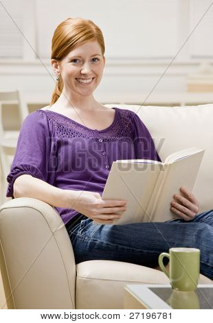 Relaxed woman sitting on sofa enjoying reading book