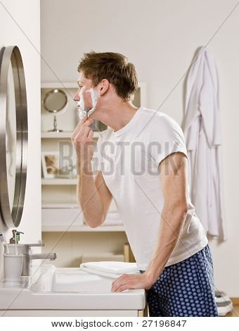 Man in pajamas in bathroom using shaving foam and shaving his face with razor