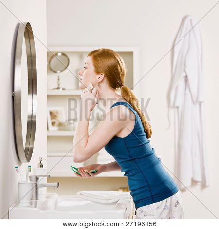 Woman in pajamas in bathroom applying blush with makeup brush