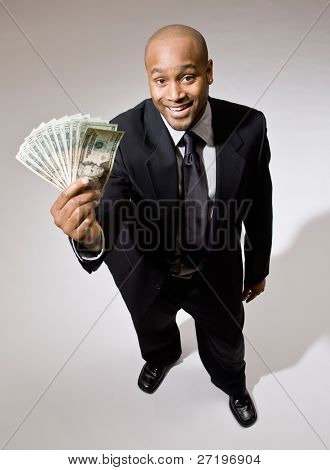 Lucky, wealth businessman excitedly holding group of twenty dollar bills