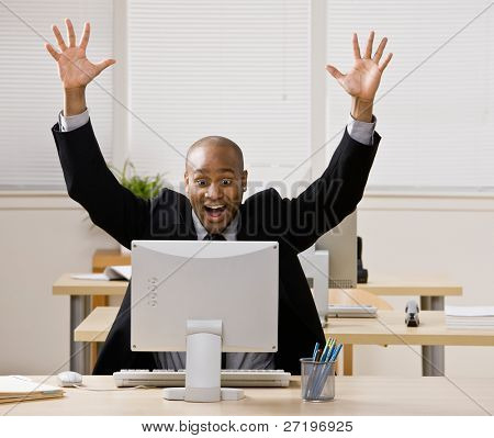 Excited businessman sitting at desk cheering and celebrating his success