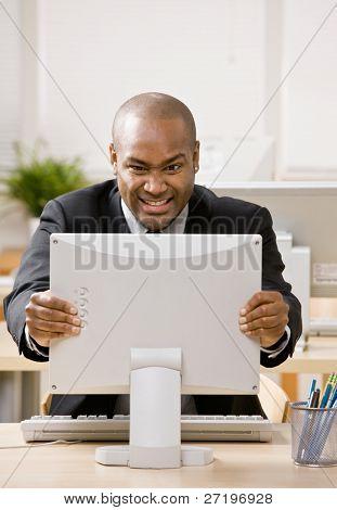Empresario frustrado, enojado, hacer muecas en el monitor de la computadora