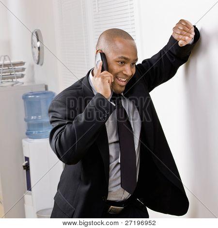 Confident Businessman stützte sich auf Wand sprechen auf Handy