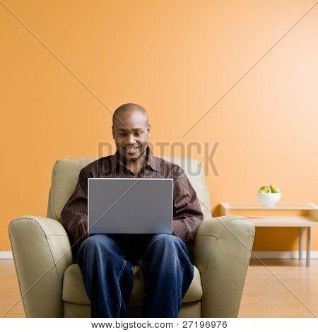 Confident man typing on laptop in livingroom
