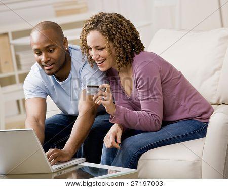 Casal feliz usando cartão de crédito para compras online convenientemente
