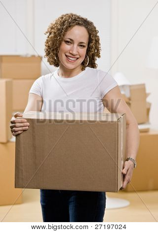 Happy woman moving into new home carrying cardboard box
