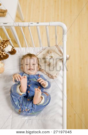 Toddler boy unhappy about taking a nap in crib in bedroom