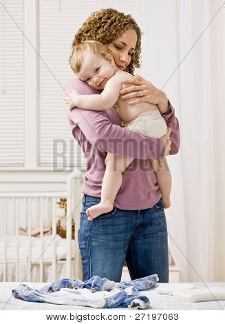 Devoted mother hugging and comforting her son in bedroom