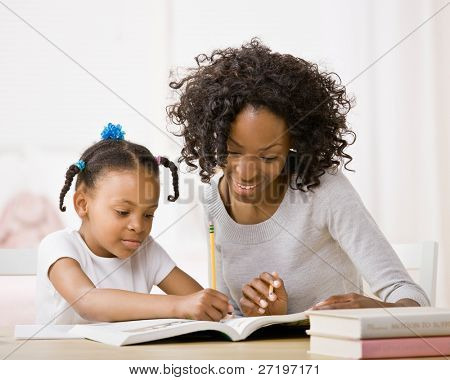 Devoted mother helping daughter do homework in workbook