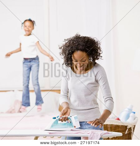 Housewife ironing laundry while mischievous girl jumps on bed
