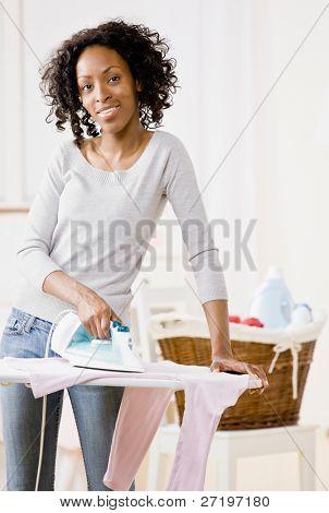 Housewife ironing laundry on ironing board