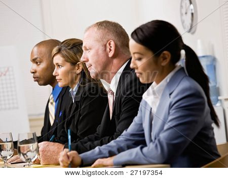 Serious co-workers listening during meeting in conference room