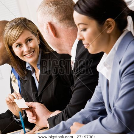 Confident businesswoman handing co-worker business card in meeting