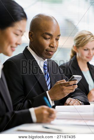 Mensajes de teléfono celular en la sala de conferencias de texto empresario serio