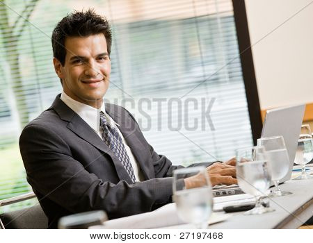 Confident businessman sitting in conference room working on laptop