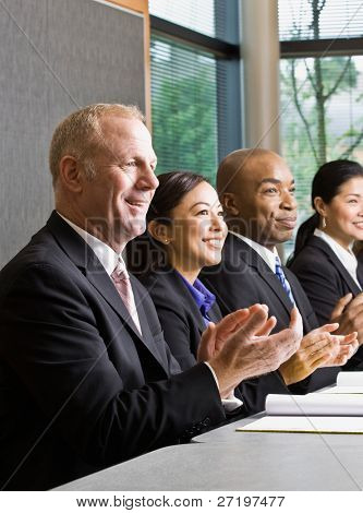 Multi-ethnic co-workers sitting in a row, applauding at conference table