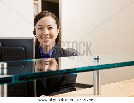 Smiling receptionist with telephone earpiece working at desk in office