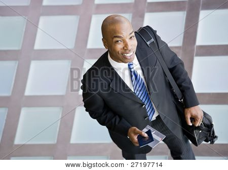 High angle view of happy African businessman with briefcase and passport traveling
