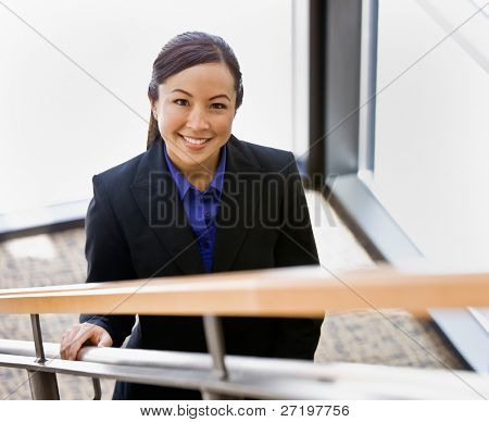 High angle view of happy Asian businesswoman ascending stairs