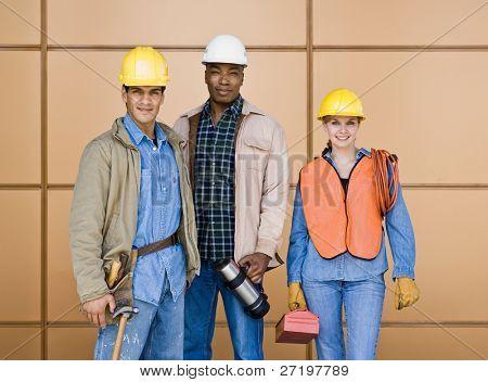 Trabajadores de la construcción multiétnica posando en hard-hats con herramientas