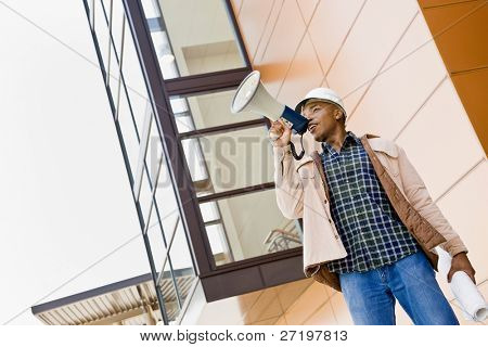 Low angle view of African construction worker making announcement into bullhorn