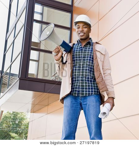 Low angle view of African construction worker holding bullhorn and blueprints