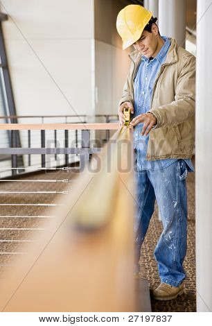 Construction worker carefully taking measurement with measuring tape