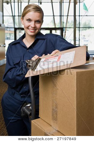 Friendly delivery woman in uniform with stack of cardboard boxes and shipping receipt