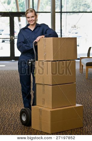 Delivery woman in uniform posing with stack of cardboard boxes on dolly