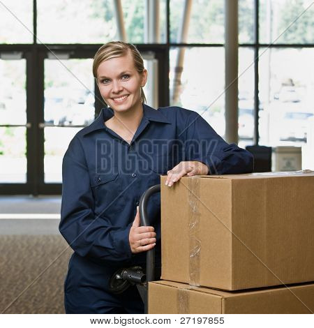 Friendly delivery woman in uniform posing with stack of cardboard boxes on dolly