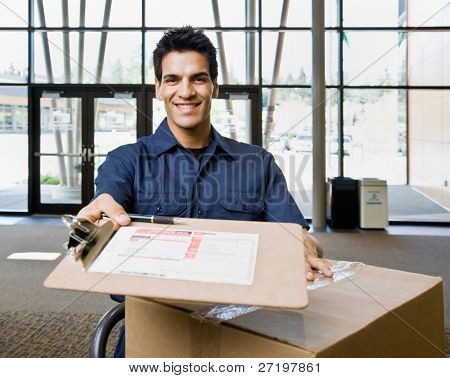 Friendly delivery man in uniform with stack of cardboard boxes and shipping receipt