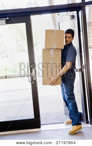 Delivery man in uniform carefully carrying stack of cardboard boxes through door
