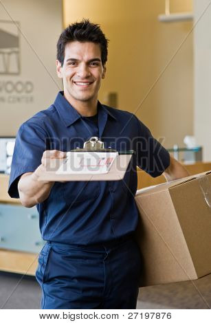 freundliche Lieferung Mann in einheitliche Versand Eingang zu präsentieren und halten Karton