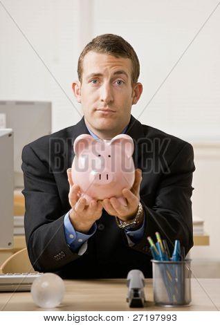 Empresário preocupado segurando o cofrinho esperando para poupança futura