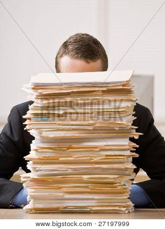 überarbeitet, frustriert Businessman looking at Haufen von Datei-Ordner
