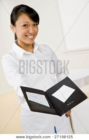 Happy waitress holding out restaurant bill and receipt