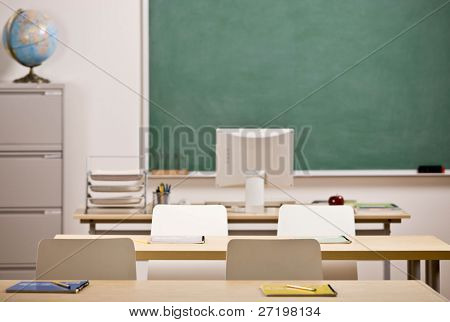 Desks, chairs, blackboard and computer in empty school classroom